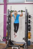 Bodybuilding. Strong fit woman exercising in a gym - doing pull-ups.. Royalty Free Stock Image