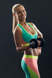 Bodybuilding. Strong fit woman exercising with. Bodybuilding. Strong fit woman smiling and exercising with dumbbell. Blonde girl lifting weights studio shot on Royalty Free Stock Image