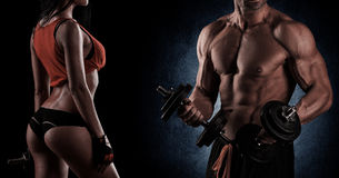 Bodybuilding. Strong man and a woman posing on a black backgroun. Young beautiful couple, bodybuilding, posing in front of the camera, sexy, strong royalty free stock photo