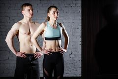 Bodybuilding. Strong man and a woman posing on a brick wall background. royalty free stock photos