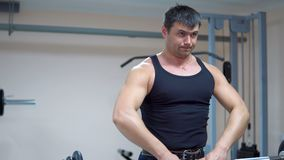 Bodybuilding. Thrust rod to the chin. A man in black clothes is training with a barbell in the gym. Deltoid muscles training. Thrust rod to the chin stock video