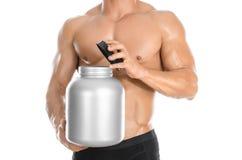 Bodybuilding- und Sportthema: der hübsche starke Bodybuilder, der ein Plastikglas mit einem trockenen Protein hält und Geste zeig lizenzfreies stockfoto