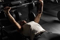 bodybuilding Uomo barbuto che si trova facendo la stampa di banco alla palestra con il bilanciere concentrato fotografie stock libere da diritti