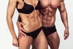bodybuilding Uomo forte e una donna che posa sul fondo bianco Immagine Stock