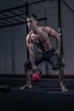 Bodybuilding, vlakke bank, de oefening van de Ketelklok Royalty-vrije Stock Fotografie