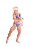 Bodybuilding woman. A strong blond woman in an blue bikini standing bare foot in the Royalty Free Stock Images
