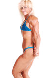 Bodybuilding woman. A strong blond woman in an blue bikini, standing bare foot in Stock Images