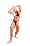 Bodybuilding woman. A strong blond woman in an black bikini, standing bare foot in Stock Image