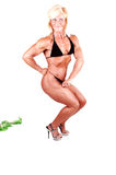 Bodybuilding woman. A blond muscular bodybuilding girl standing in the studio shooing her Royalty Free Stock Photography