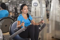 Bodybuilding. woman exercising in gym with exercise-machine Stock Images