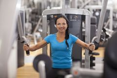 Bodybuilding. woman exercising in gym with exercise-machine. Royalty Free Stock Photography