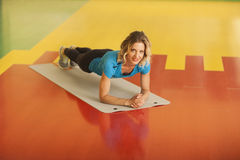 Bodybuilding. woman exercising on mat in fitness class. Female workout in gym doing plank Royalty Free Stock Photography