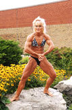 Bodybuilding woman on location. An blond bodybuilding woman sitting on a big rock and flowers behind her Stock Photo