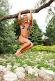 Bodybuilding woman on location. An blond bodybuilding woman hanging on a branch of a big tree, in a bikini Royalty Free Stock Photos