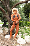 Bodybuilding woman on location. An blond bodybuilding woman standing on some rocks in front of trees Royalty Free Stock Photos