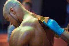 Bodybuildingkonkurrens i kulisserna: konkurrenten som oljas och, fejkar solbrännan som appliceras till hud Arkivbilder