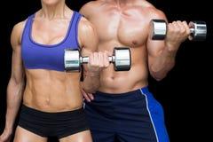 Bodybuildingspaar het stellen met grote dumbells Stock Foto's