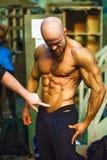 Bodybuildingstrid bak platserna: konkurrenten förbereder sig för kapaciteten Royaltyfri Foto
