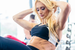 Bodybuildingsvrouw die zitten-omhoog in geschiktheidsgymnastiek doen Royalty-vrije Stock Fotografie