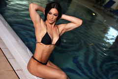 Bodyfitness champion of WORLD LADIES CUP. Fashion photo of bodyfitness champion of WORLD LADIES CUP posing beside a swimming pool Stock Photo