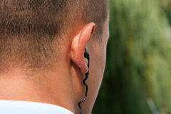 Bodyguard. Back of male head with earphone royalty free stock image