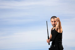 Portrait of a bodyguard. Bodyguard with black uniform and a crowbar stock photo