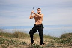 Bodyguard in the sand. Bodyguard with black uniform and a crowbar stock photo