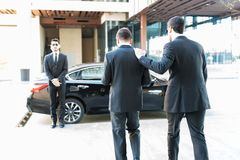 Bodyguard Giving Service To Employer. Dedicated security agent providing protection to popular celebrity while walking towards car royalty free stock image