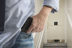 Bodyguard with gun protects client. Against an s water closet door background royalty free stock photography