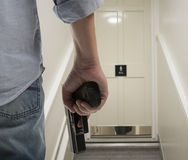 Bodyguard with gun protects client. Against an s water closet door background stock photos