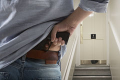Bodyguard with gun protects client. Against an s water closet door background stock images