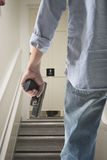 Bodyguard with gun protects client. Against an s water closet door background stock image
