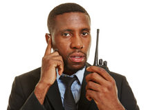 Bodyguard with headset and radio. Black bodyguard with headset and radio working for personal security royalty free stock images