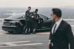 Bodyguard helping businessman to sit. In black car royalty free stock photo