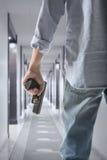 Bodyguard. Man holding gun against an corridor background royalty free stock image