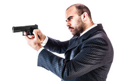 Bodyguard. Portrait of a classy businessman or mobster or security guard holding a gun isolated over a white background stock photos