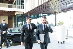Bodyguard Ready To Provide Instant Protection. Male employer using smartphone while protection specialist walking by him royalty free stock photo