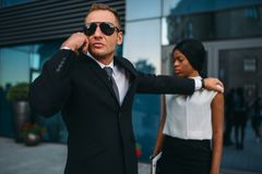 Bodyguard requests support for client protection. Serious bodyguard in suit and sunglasses requests support on earpiece for female client protection. Security royalty free stock image