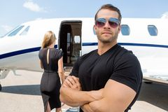 Bodyguard Standing Against Woman And Private Jet. Confident bodyguard wearing sunglasses while standing against women and private jet stock images