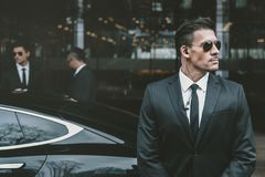 Bodyguard standing at businessman car and reviewing. Territory stock images