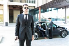 Bodyguard Staying Alert While Colleague Opening Car Door For VIP. Protection specialist observing environment while colleague escorting VIP in city royalty free stock photography