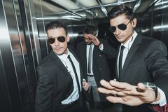 Bodyguard stopping paparazzi when celebrity standing. In elevator stock photos
