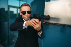 Bodyguard in suit and sunglasses with gun in hands royalty free stock photography
