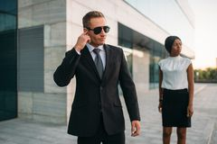 Bodyguard in sunglasses and black business woman. Personal bodyguard in sunglasses and black business woman. Security guard is a risky profession, guarding royalty free stock photography
