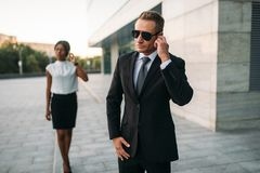 Bodyguard in sunglasses and black business woman royalty free stock photography