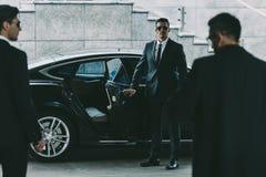 Bodyguard in sunglasses opening car door. To businessman stock image