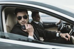 Bodyguard in sunglasses talking by portable radio while sitting. In car stock image