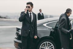Bodyguard talking by portable radio. Near businessman car stock photography