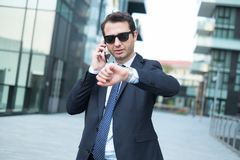Bodyguard wearing black sunglasses checking time. Modern business checking time on his wristwatch royalty free stock images