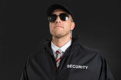 Bodyguard Wearing Sunglasses And Earpiece. Young Male Bodyguard Wearing Sunglasses And Earpiece Over Black Background Royalty Free Stock Images